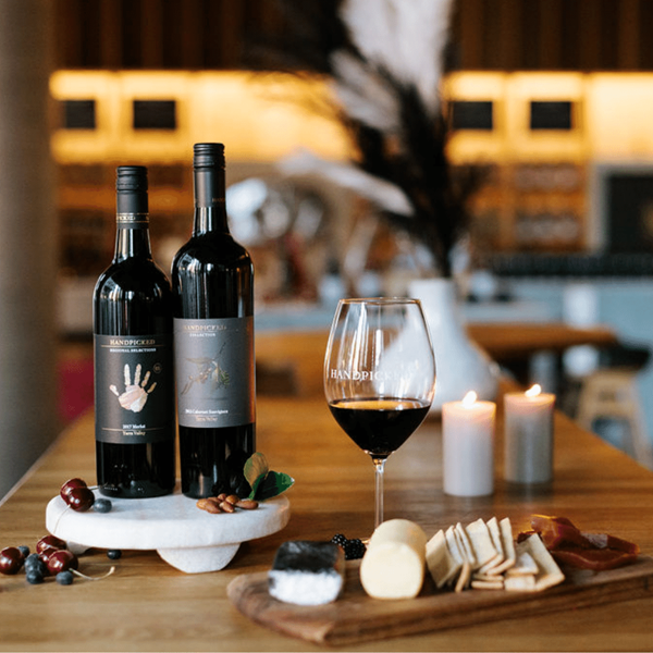 Bottles of Yarra Valley wines with cheese and crackers on a wooden table