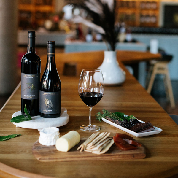 Two bottles of Handpicked Collections Red Wines with matching cheeses
