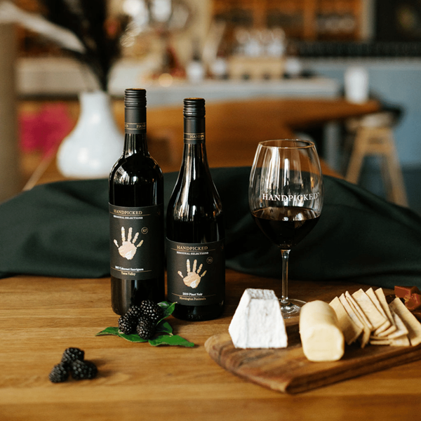 Two Bottles of Handpicked Regional Selections in a lifestyle setting with matching cheeses