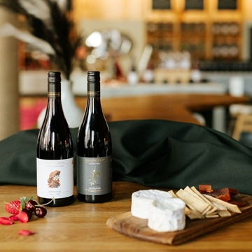 Two bottles of Handpicked Oregon Pinot Noir with matching cheeses on a wooden table