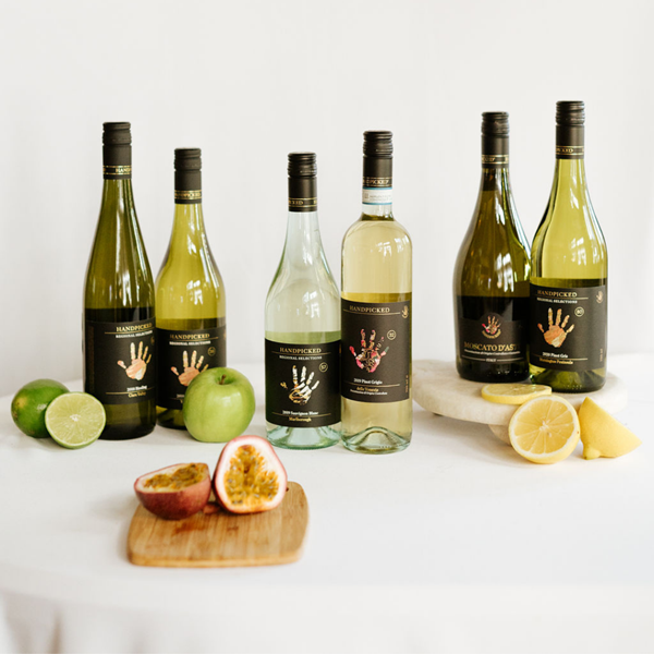 6 bottles of white wine with lime and lemons on cutting boards
