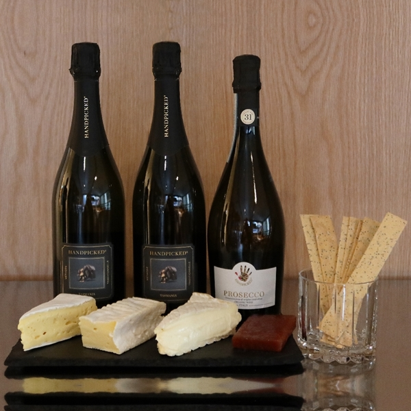 Two Bottle front view of Handpicked Tasmanian Sparkling and a bottle front view Prosecco with matching cheese